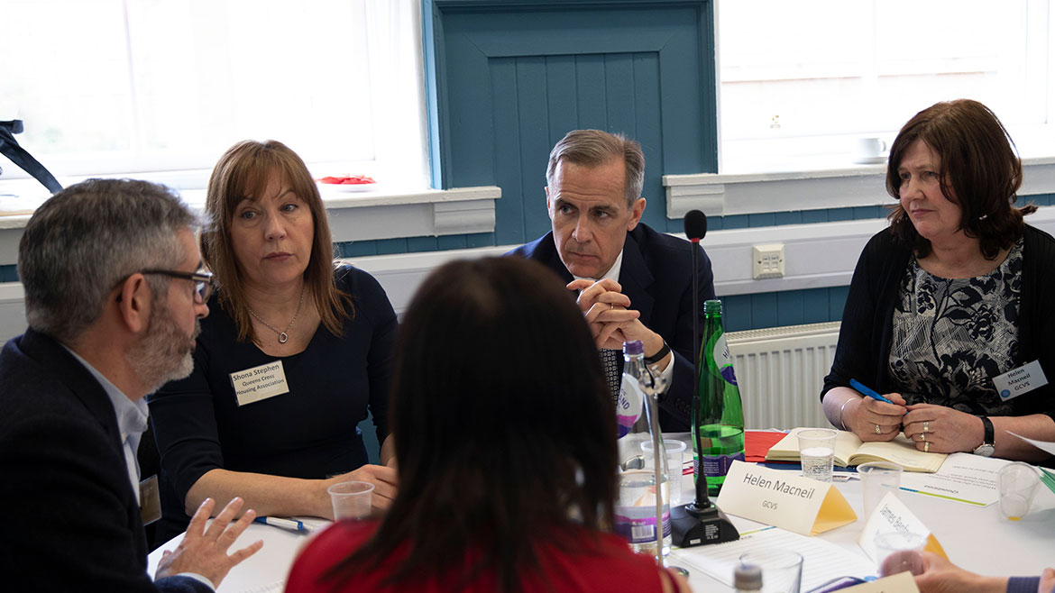 Mark Carney involved in group discussions at the community forum in Glasgow