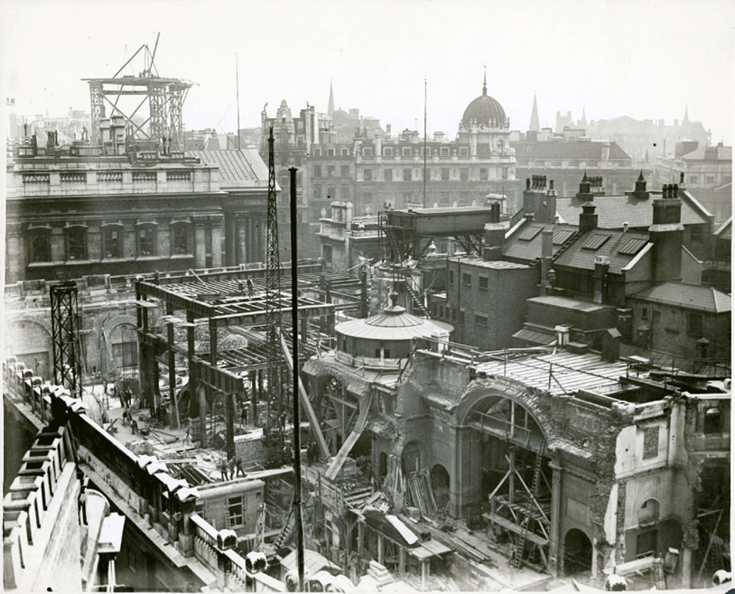 This aerial photograph looks down towards the south east corner of the Bank of England during its rebuilding. It overlooks the top of the wall that runs along Bartholomew Lane, whilst the Royal Exchange and 1 Cornhill at Bank junction can be seen in the distance.