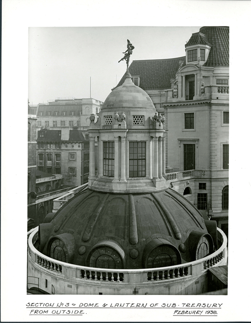 An exterior view of the dome and lantern of the Sub-Treasury following completion. The statue of Ariel can be seen on the top. Named after Shakespeare's 'The Tempest', Ariel had 'magic invisible spirit' according to architect Herbert Baker and represented 'the ethereality of market credit and paper money.'