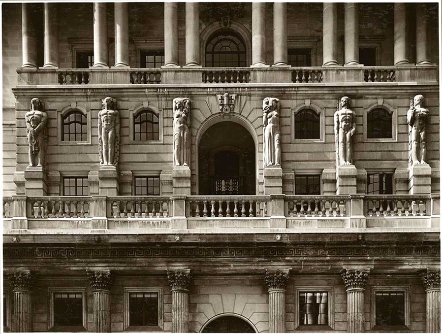 This photograph shows the detail of the portico sculptures which adorn the front of the Bank of England. These were designed by Charles Wheeler, R.A, along with many other sculptures that feature in Herbert Baker's Bank.