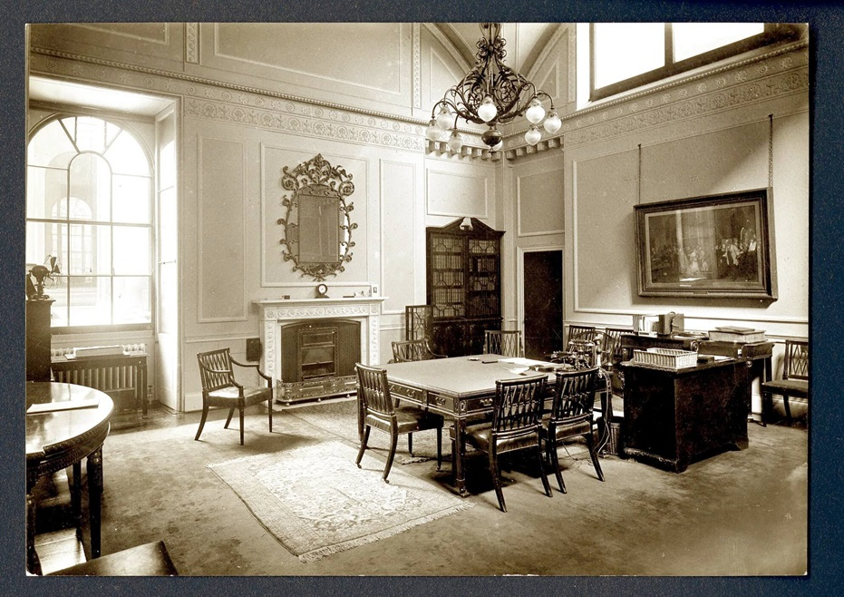 A bright and spacious Governor's Room furnished with an ornate chandelier