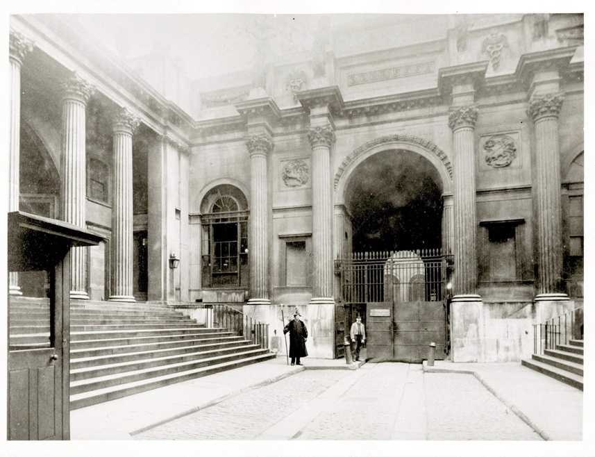 A messenger and gatekeeper can be seen standing at the entrance to the old Bullion Yard in Lothbury Court