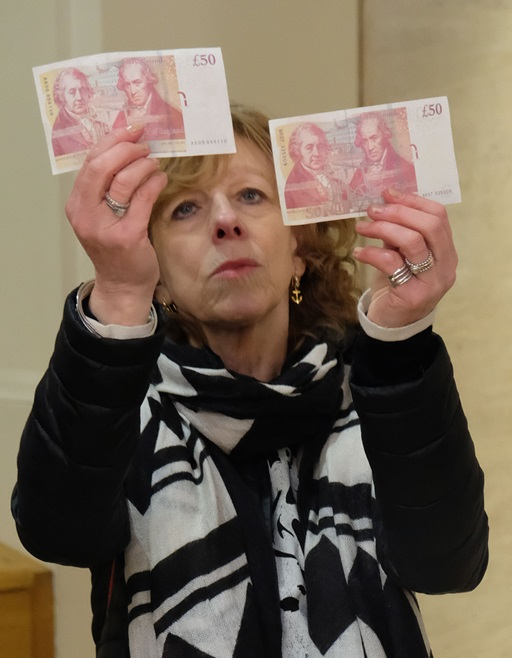 Lady inspecting £50 notes